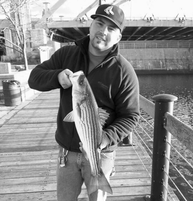 "Tommy Pelto of Tiverton, RI with one of the striped bass he caught this Saturday when fishing in the upper reaches of the Providence River.  Tom said, ""There were tons of pogies in the Providence River."""
