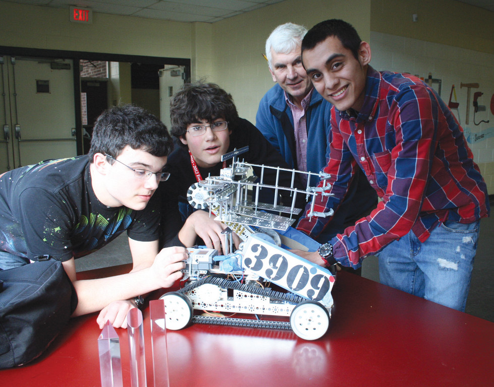 IN THE WINNING CIRCLE: The Toll Gate team made the finals of the competition held Saturday at the New England Institute of Technology. Seen here with their robot from left are: team members Michael Smith, Jamie Allstrom and Jeffery Castellanos. Looking on is Dennis Dubee, department chair of technical education who assisted the team.