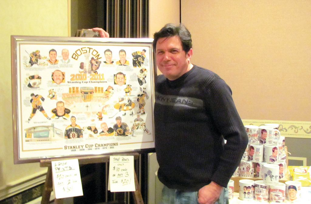 PICTURE PERFECT: Sports cartoonist Frank Galasso stands aside his drawing of the Boston Bruins' after winning the 2011 Stanley Cup championship. He was one of five Cranston residents who had displays at the 36th annual Cranston Sports Collectors Show.
