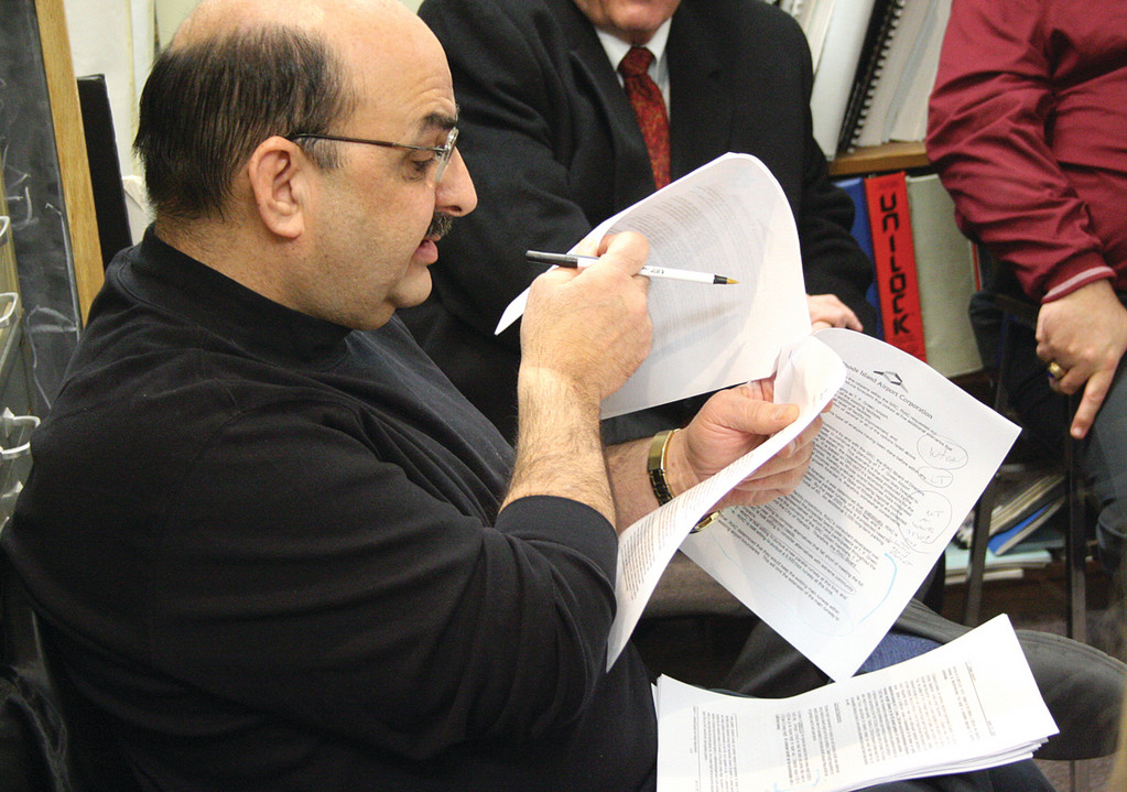 MAKING HIS POINTS: Resident Michael Zarum leafs through documents while making points yesterday to the council committee overseeing litigation appealing the decision to build a runway extension.