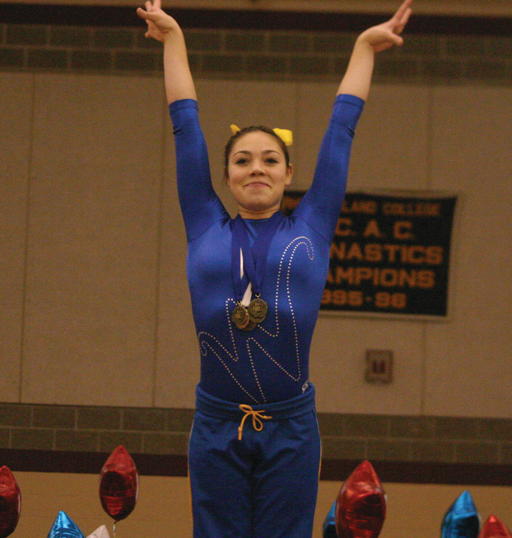 SALUTE: Vets freshman Candis Kowalik takes her spot on the podium after winning the gymnastics all-around championship on Sunday. She tallied the second-highest score in state history.