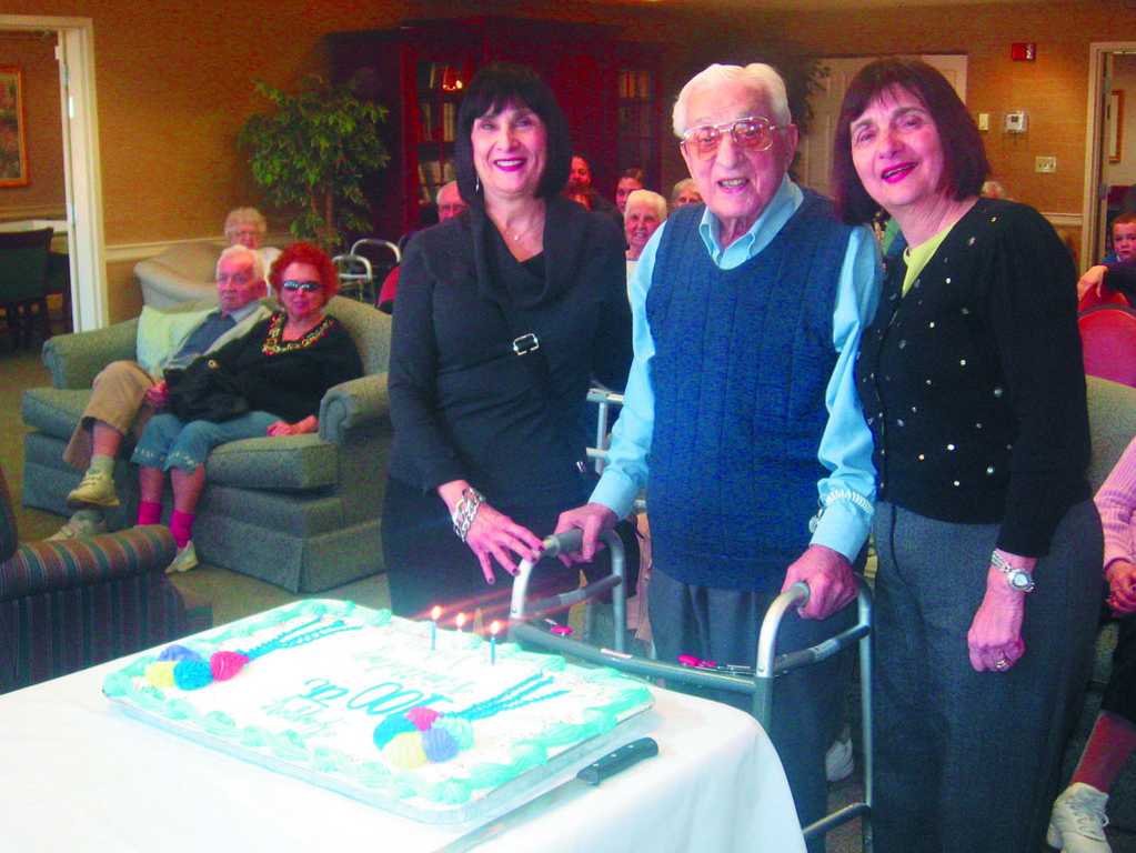 BIRTHDAY BOY: West Bay Retirement Living resident John Lombardi turned 100 years olds on Monday and was treated to a celebration with his loved ones in the Great Room of the senior community. Among his guests were his daughters, Joan Rozen (left) and Judy Campbell.