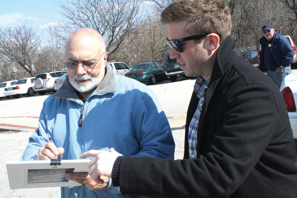 GARNERING SIGNATURES: Ryan Patrick Kelley, who is seeking to become a delegate to the Democratic National Convention, gathered signatures yesterday at City Hall. Here, Warwick resident John Lamanta signs Kelley's papers.
