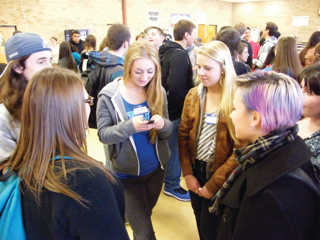 WHAT'S YOUR NUMBER? Danish exchange students Karoline Parker (left) and Astrid Ramussen swap numbers with their new Pilgrim High School friends.