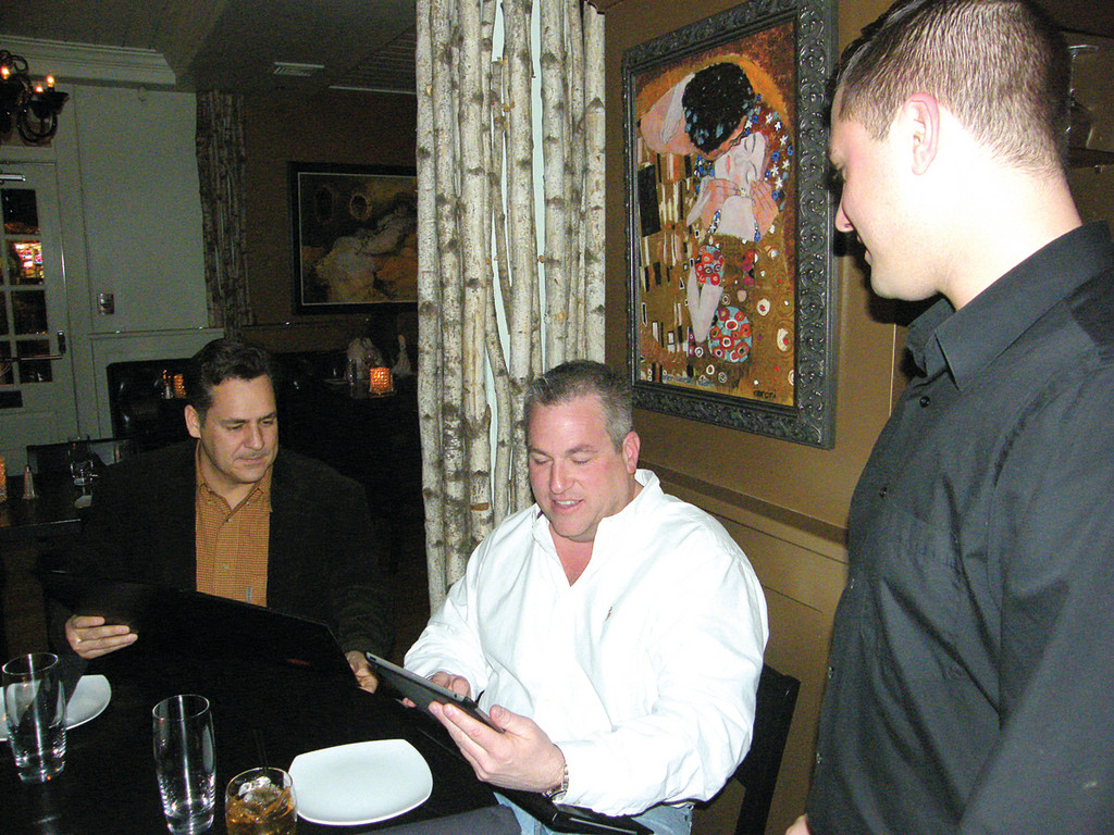 TABLESIDE TECHNOLOGY: Mike Dellagrotta (left) and Allen Gammons, Jr. look at an iPad to check out the special at Beso's Tea House in East Greenwich. Server Gus Charos awaits their order, which he can send directly to the kitchen via the iPad's wireless network.