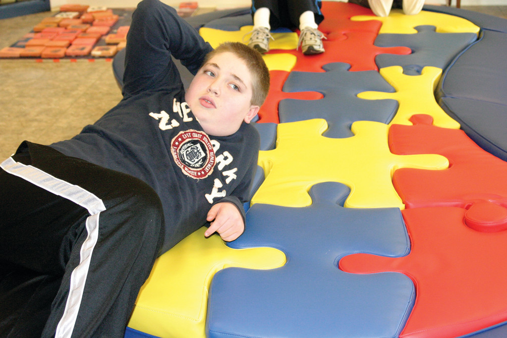 STRIKE A POSE: Dylan Barbosa, 13, has some fun on a giant foam puzzle, which is located at the entryway of the center. He is one of 58 students.