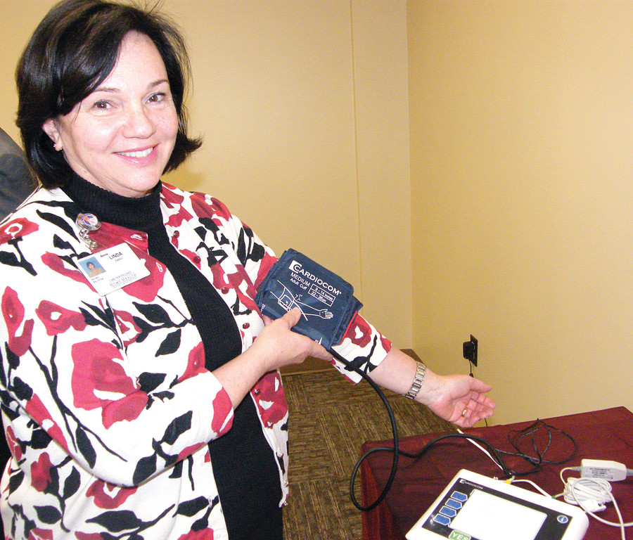 OFF THE CUFF: Linda Zabbo, program manager at the VNA of Care New England demonstrates the telemonitoring technology. The system asks the patient questions, monitors weight and blood pressure, and communicates data wirelessly to the VNA.