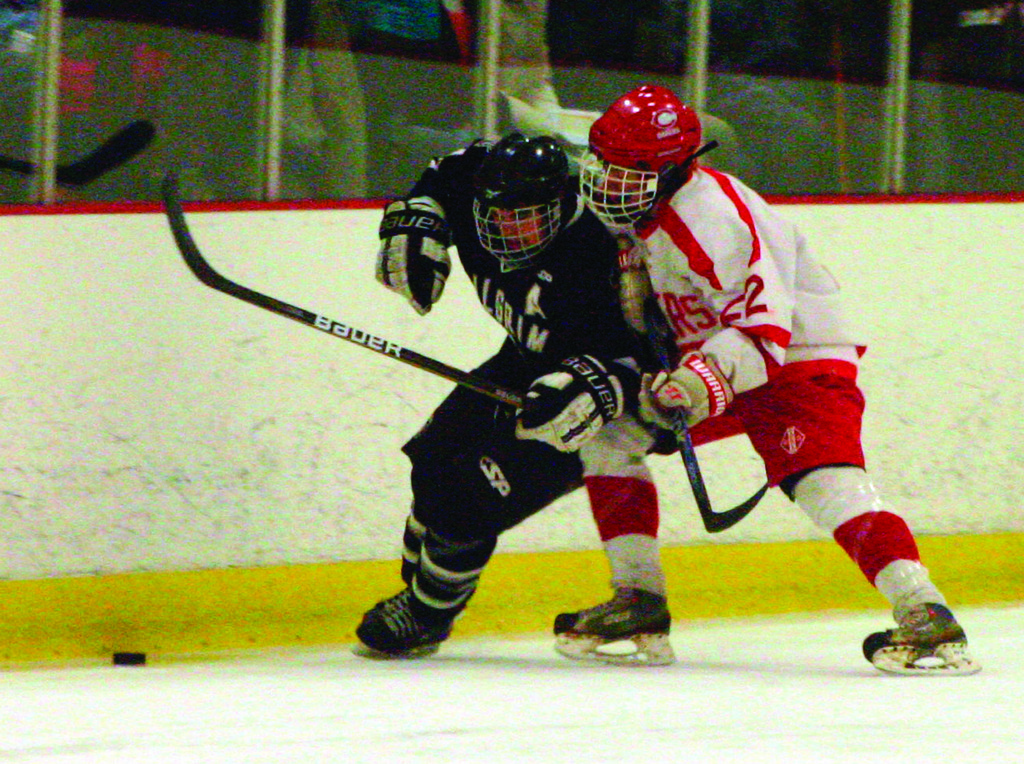 TANGLED UP: Pilgrim's Nick McGuirl tries to get to the puck as Coventry's Corey Rogers stays close in game one of the Division II semifinals. The Pats lost game one 2-0 and dropped game two 6-1 as Coventry swept into the championship series.