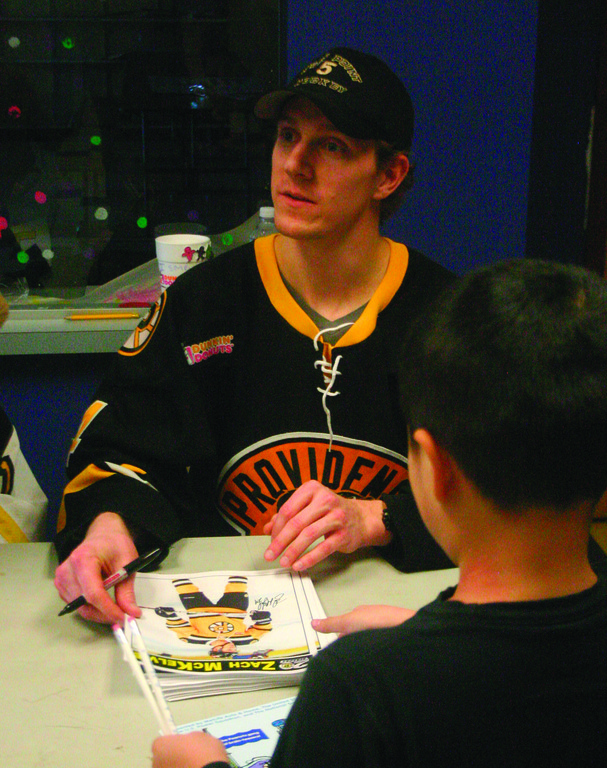 Zach McKelvie signs autographs.