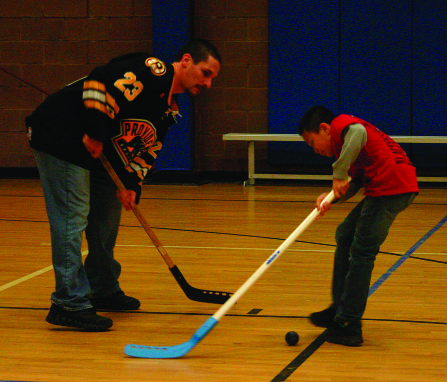 Trent Whitfield plays floor hockey with Justin Chen.