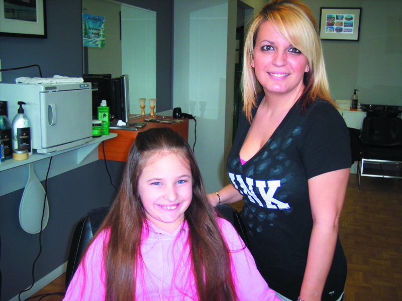 "Meet Kristin, a familiar face at this clean and affordable barber shop, with her sometimes ""assistant"" Sarah."
