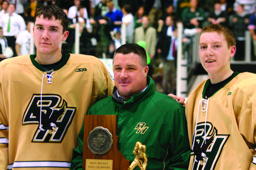 Captains Justin Finan (left) and Nick Bodziony join head coach Jim Creamer in accepting the state championship trophy Monday night.