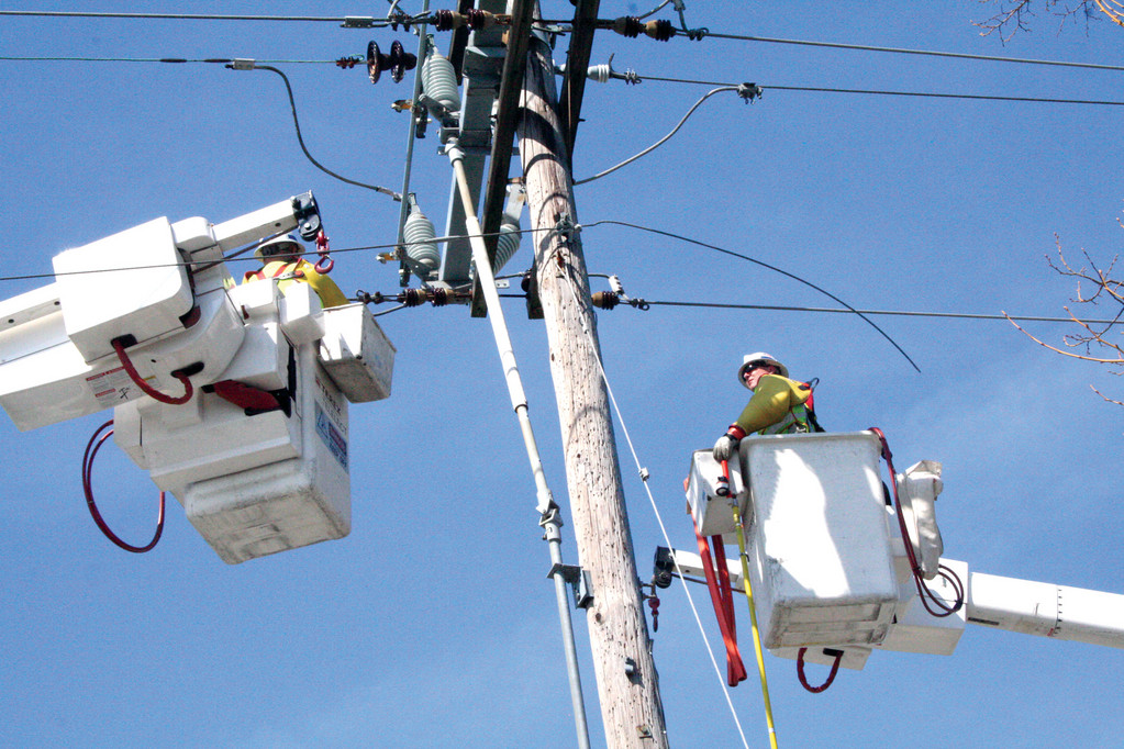 HIGHWIRE ACT: National Grid linemen John Gardner, left, and Kendal Yew work to restore power.