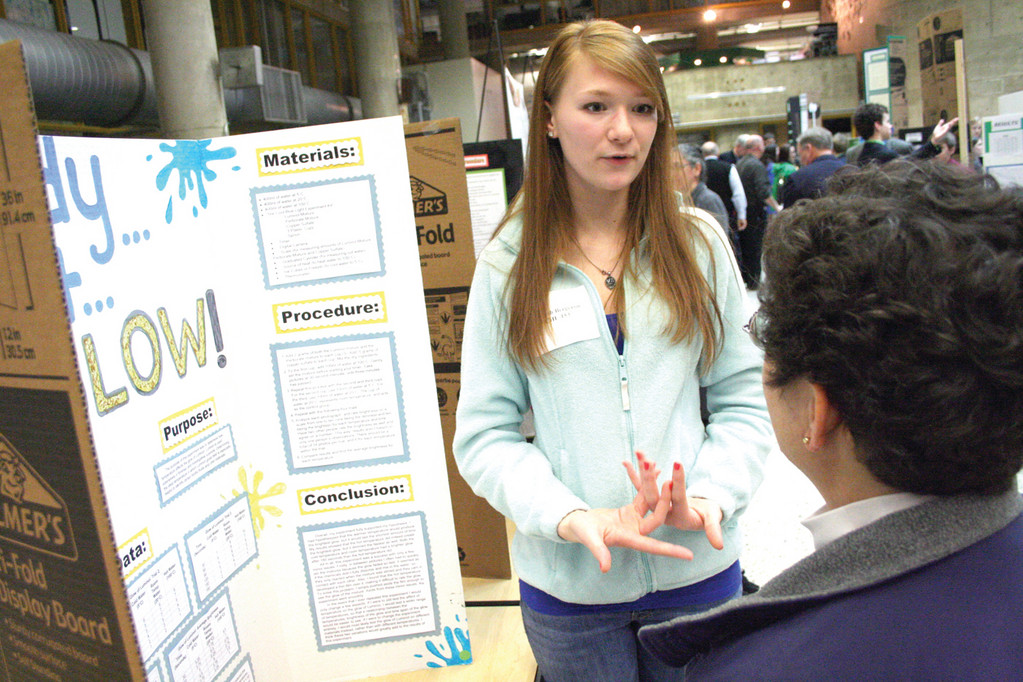 MORE HEAT, A BRIGHTER LIGHT: Hannah Bergeron of Johnston explains her project to judge Helaine Hager.
