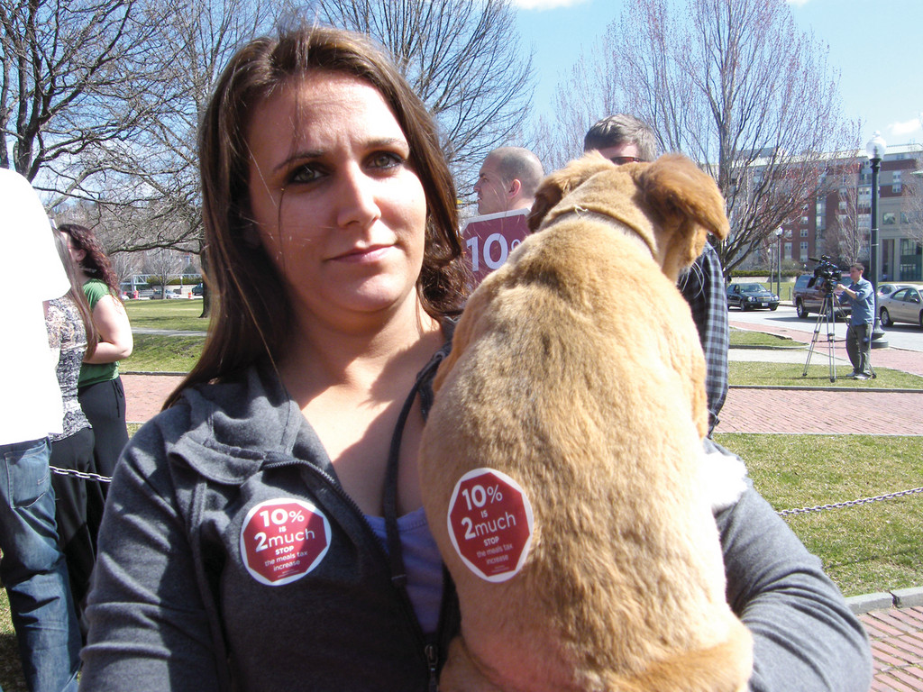 "SIT, STAY, PROTEST: Natasha Greco representing Harry's Bar and Burger holds Fifi, her dog, at yesterday's protest on the State House lawn. Fifi bears a sticker that reads ""10% is 2 much!"""