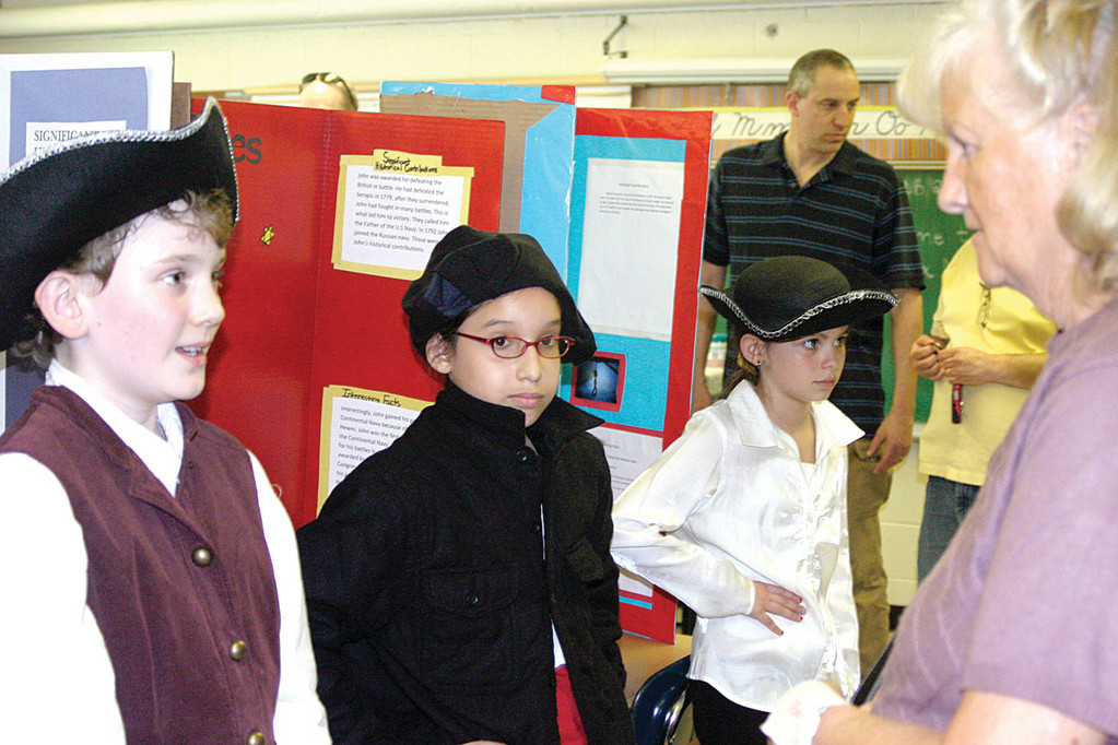 "HISTORY COMES ALIVE: Sixty-five students from the three fifth grade classes at Cedar Hill Elementary School posed as some of the most famous Revolutionary War and figures characters from colonial times during a ""wax"" museum held at the school Friday afternoon. From left are Teddy Stone, 11, as Paul Revere; Alexxa Rivera, 10, as John Paul Jones; and Allie Lewis, 10, enjoyed performing as Nathan Hail. Visitor Carol Lynch looks on."