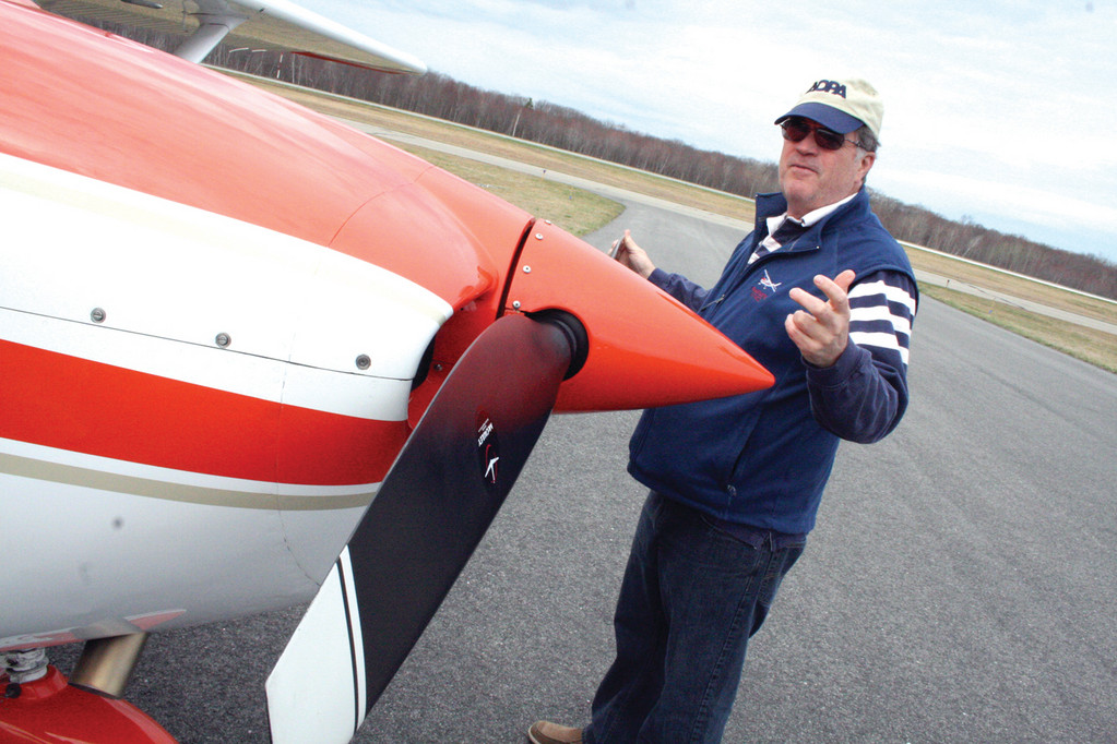 PREFLIGHT CHECK: Howard McVay checks over his plane before taking off for lunch on Block Island.
