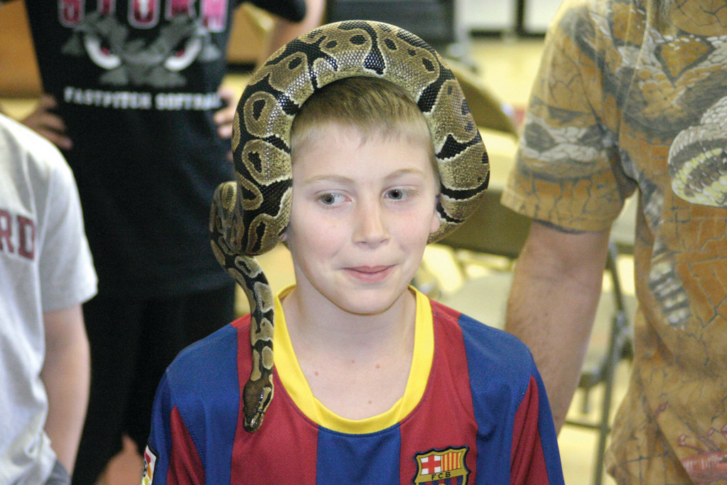 SLITHERY CAP: Fifth grader Dan Lajoie, 11, has fun with Jeffrey the Ball Python. Since Dan�s grandfather died of Leukemia five years ago, he saves his money in a �rainy day jar� and makes a donation to Pennies for Patients.