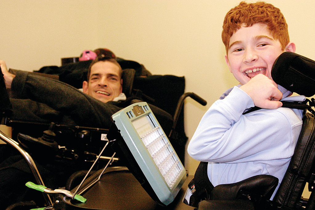 CLEVER COMMUNICATION: At left is Jim Petrone, 41, a client of West Bay Residential Services who has cerebral palsy and uses a communication device, the DynaVox 3100, to converse with others. He recently began working with Colby, 9, a third grade student at Meeting Street School in Providence who also has cerebral palsy.