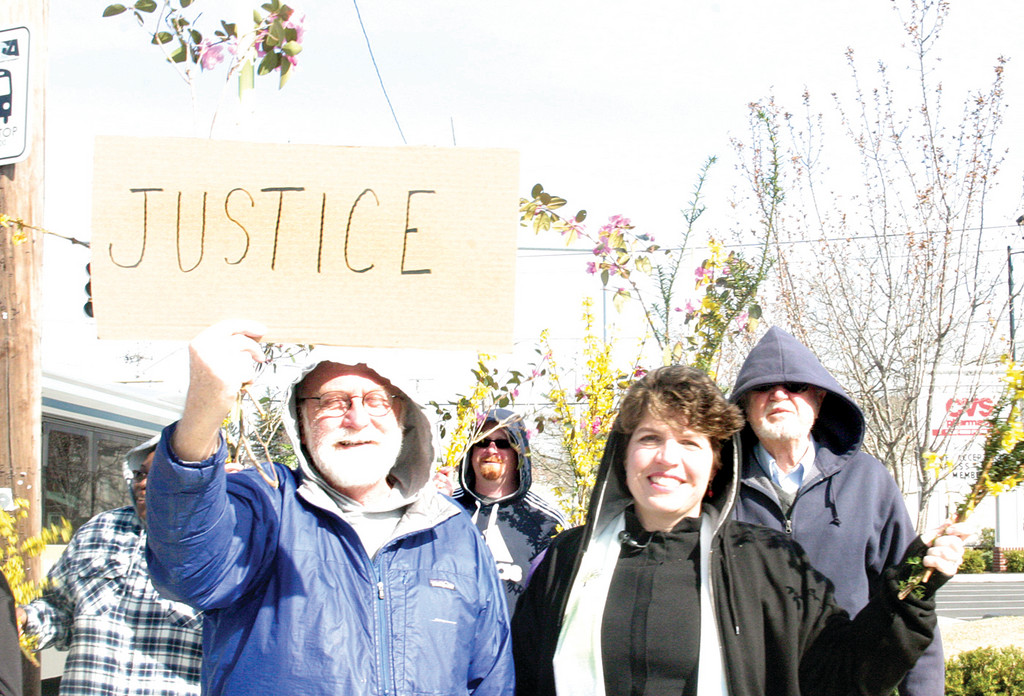 SEEKING JUSTICE: Wearing hooded sweatshirts and waving flowering tree branches, more than 30 members of Edgewood Congregational Church, United Church of Christ in Cranston marched up and down the street before weekly services on Sunday as a means to raise awareness of racial inequities. Inspired by the recent murder of Treyvon Martin, church member Jim Edwards holds a sign that reads �Justice� as Pastor Amy F waves freshly cut branches.