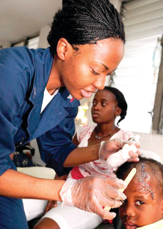 Hospital Corpsman 2nd Class Kisha Wright, assigned to USS Gunston Hall's (LSD 44) Medical Services Department, treats a child at the Killick Haitian Coast Guard Base. Gunston Hall, a Whidbey Island-class dock-landing ship, was orignally scheduled for a deployment to West Africa when it was diverted to help Haitian earthquake relief operations in 2010.