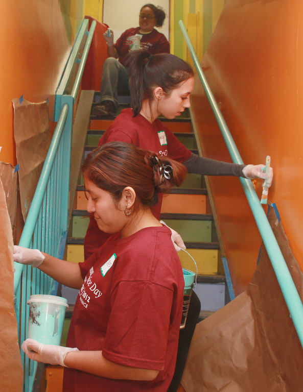 COLLEGE SERVICE DAY:  Community College of Rhode Island students Janeth Buendia (front), Amanda Lacroix and Ruth Hampton paint a stairwell at the Artists� Exchange in Rolfe Square. The site was one of eight nonprofits across the state where CCRI students, faculty and staff volunteered for the college�s sixth annual Community Service Day.