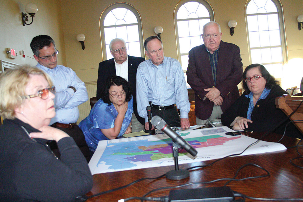 CENTER OF ATTRACTION: Council members, Donna MacDonald and a single member of the public, Tom Chadronet, view a map of the proposed redistricting of City Council Wards Tuesday evening. From left: MacDonald, Steve Colantuono, Donna Travis, Ray Gallucci, Bruce Place, Chadronet and Camille Vella-Wilkinson.