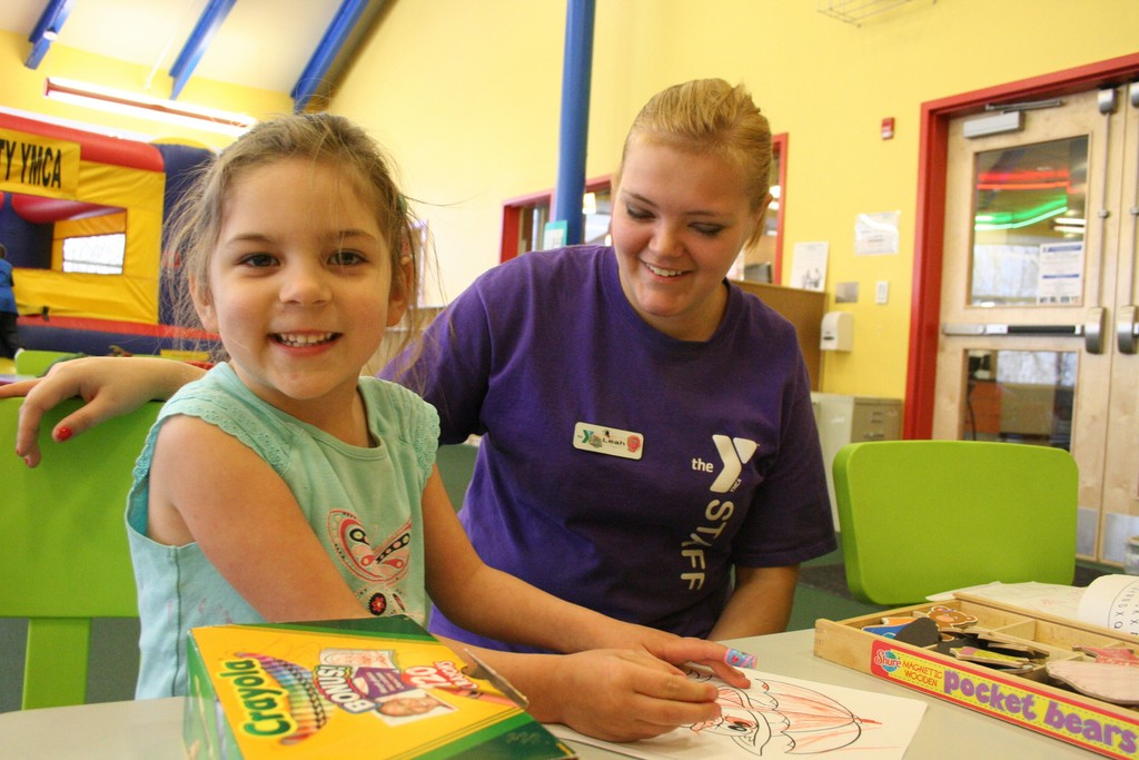 FUN TIME AT Y: Juliette Bays has fun coloring as Leah Smith of the Y staff looks on.