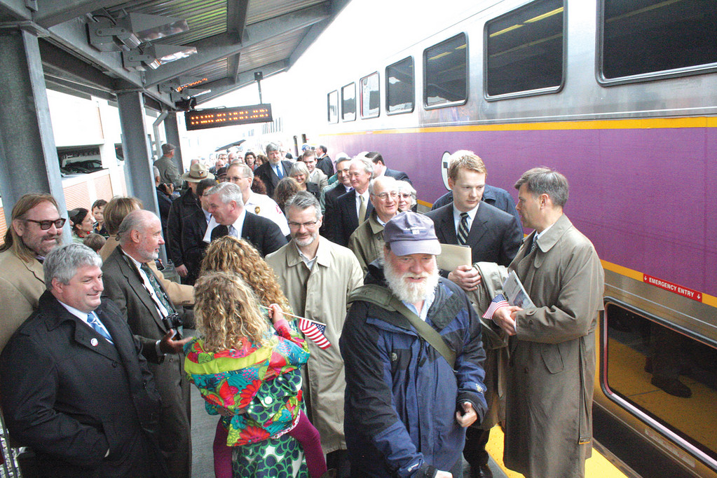 Officials who caught the MBTA train in Providence and Warwick greet those at the Wickford station yesterday, the first day of service to the new station.