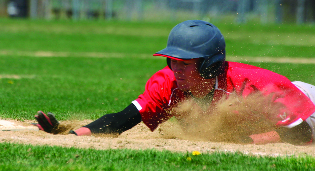 GETTING DIRTY: Toll Gate's Colin Stamps slides back to first base on a pickoff attempt in Friday's game against Barrington. The Titans lost 8-3.