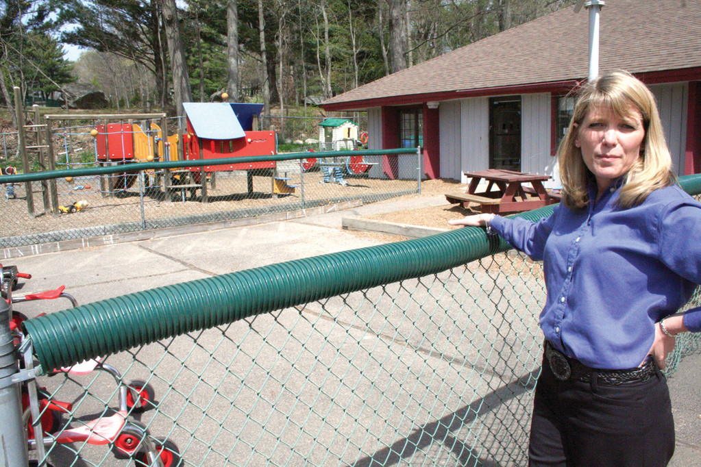 THE OLD AND THE NEW: Holly Damm looks over the existing Sargent Rehabilitation Center playground that is to be replaced by a new one on the concrete area as seen in the courtyard between buildings.