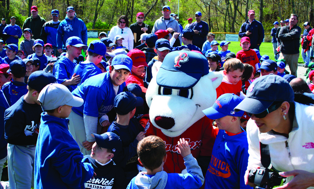 Players gather around PawSox mascot Paws.