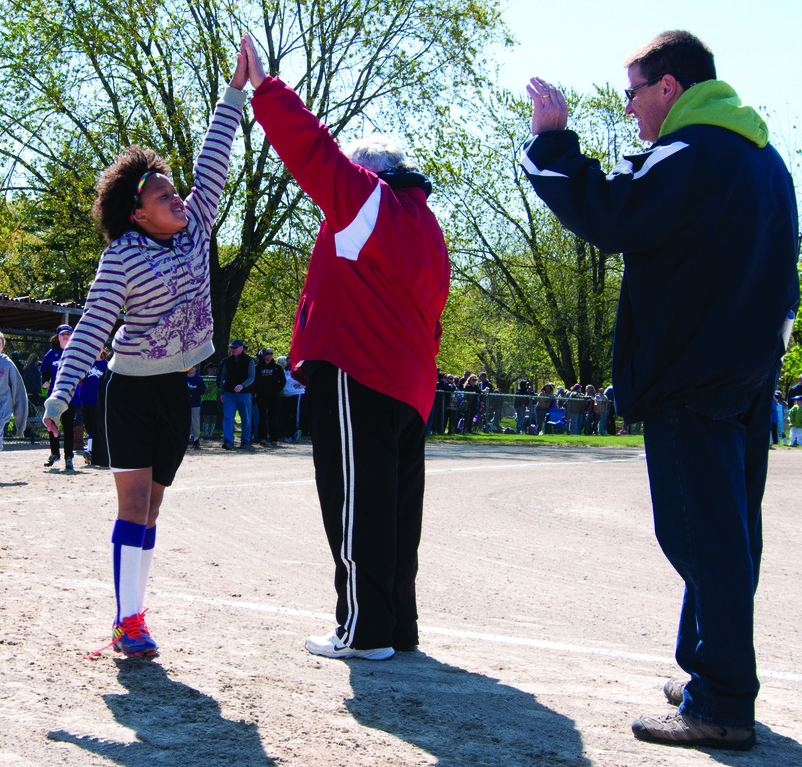 Olyvia Pendergast gives a high five to league president Chuck McCaughey.