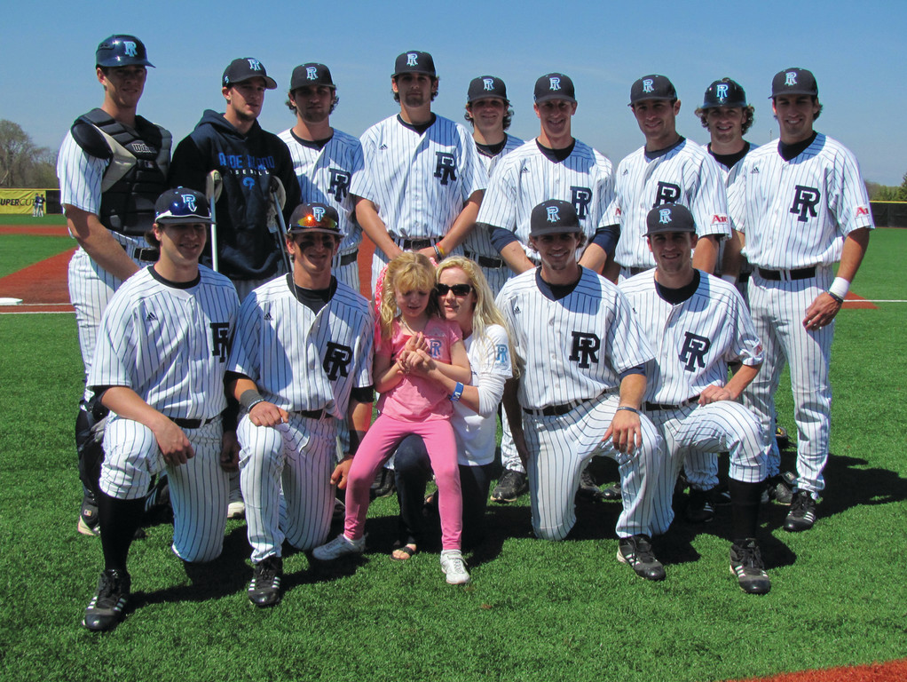 TEAMING UP: Members of the URI baseball team pose with Narelle and Delaney Foster, wife and daughter of coach Jim Foster, at the Rams' fifth annual Autism Awareness Day.