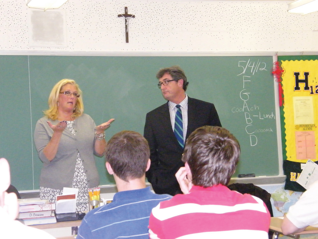 RI LAW DAY: With a cross hanging above them, the Honorable Karen Lynch Bernard of Rhode Island Family Court and Robert Craven, Esq. discussed First Amendment rights, like freedom of speech and religion with David Flaherty's sophomore honors U.S. History class at Bishop Hendricken High School on Friday as part of Rhode Island Law Day.