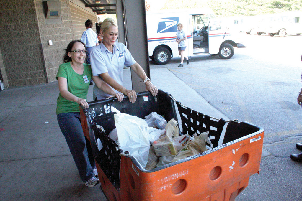 Carriers Marlene Monahan and Beth Winpenny wheel cartloads of donated food after having been offloaded from mail vans returning from Saturday�s delivery.