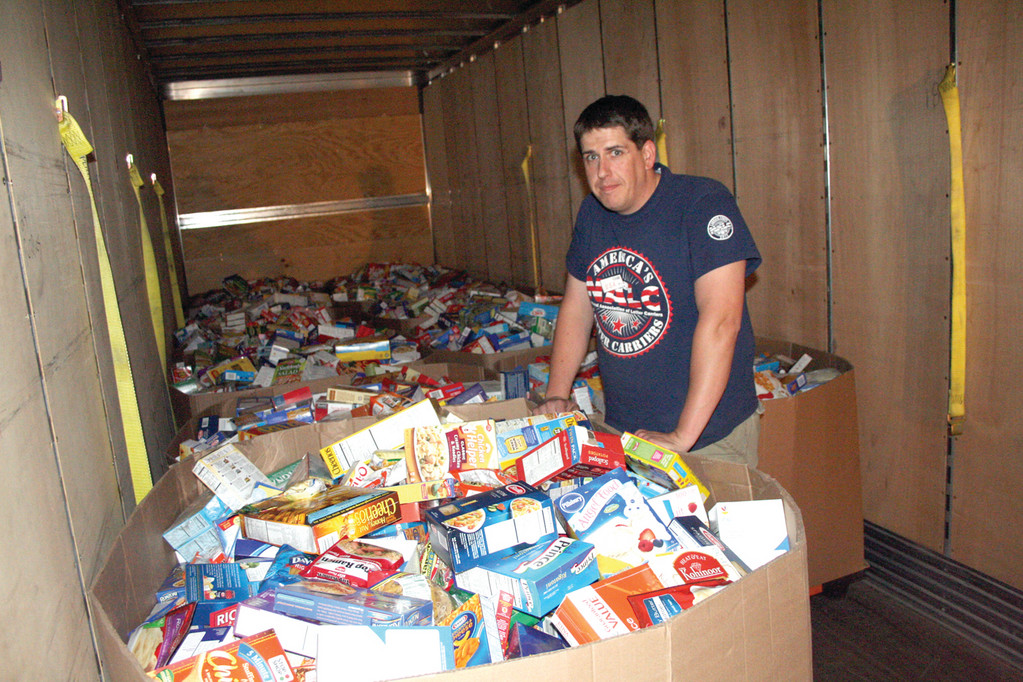 A TRAILER TRUCK FULL: Drive coordinator Jim Harrington with 12 of the large containers filled with non-perishable food and ready to be shipped to the Rhode Island Community Food Bank.