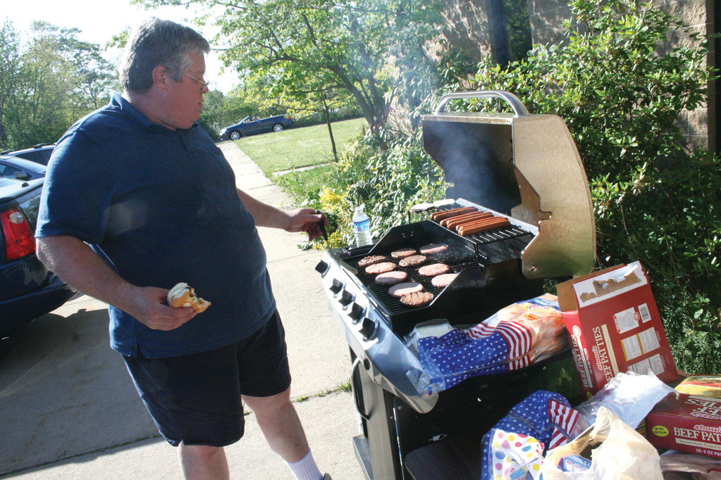 TASTE TESTER AND COOK: Paul Stromberg of Local 99 IBEW manned the grill outside Warwick�s central Post Office to provide a bite for carriers and volunteers who staffed the food drive.