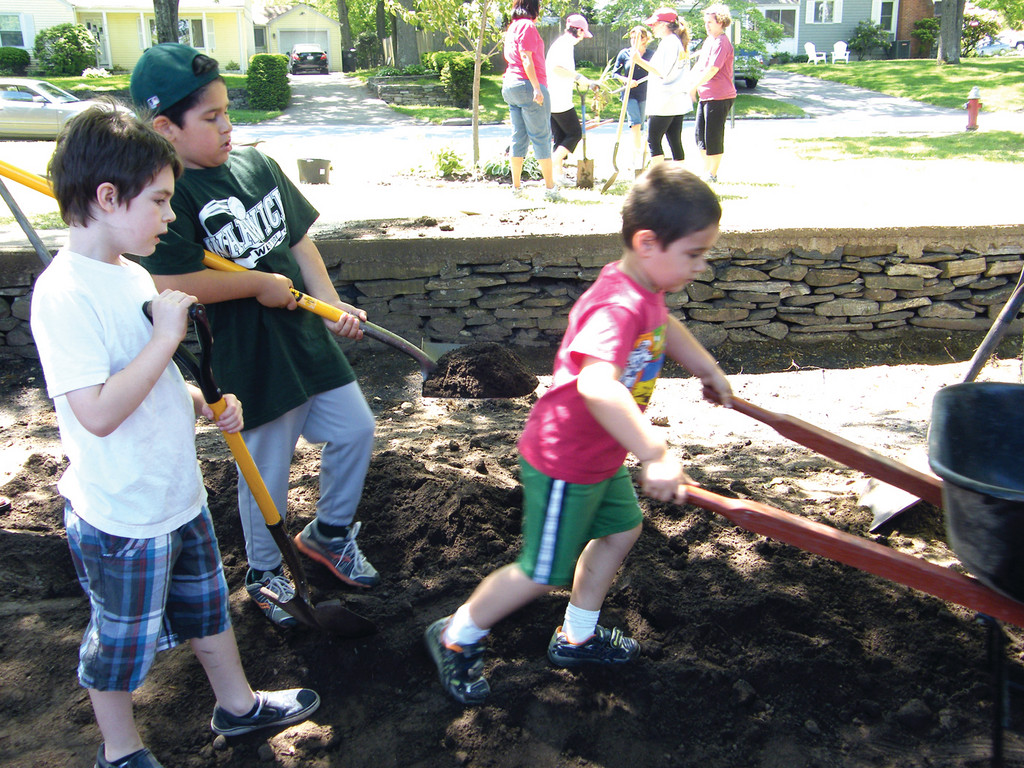 ON THE MOVE: Jacob Facente, a future John Brown Francis student, pushes a wheelbarrow while kindergartener John Maguire and first-grader Raymond Facente oversee his progress.