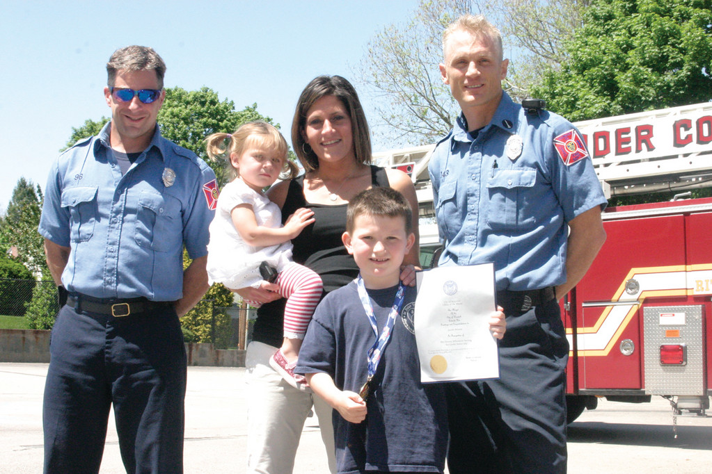LITTLE HERO: Jacob Minnis, 7, a Cranston resident and fifth grader at St. Peter's Elementary School, recently saved his sister, Gia, 1, from a horrible accident. To honor his heroic actions, two Warwick firefighters, Pvt. Rob Vallely (left) and Lt. John Halloran, visited the school Thursday and presented Jacob with a medal and citation from the city of Warwick. Jacob's mother, Kim Albanese, stands in the center holding Gia.