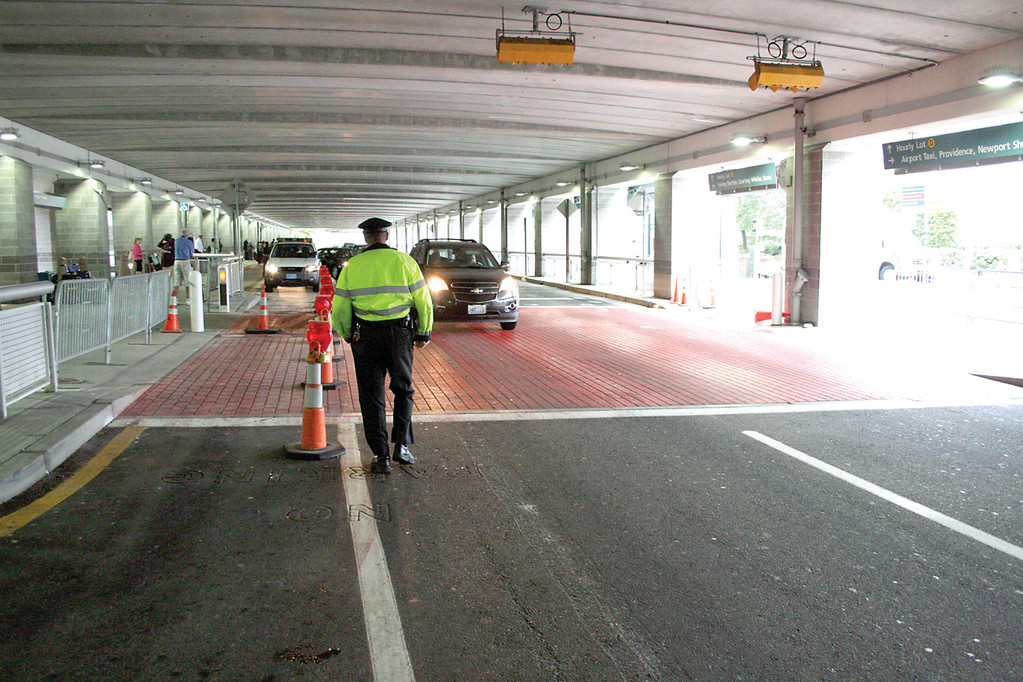KEEPS THEM MOVING: An airport police officer keeps traffic flowing at the terminal arrival area. Motorists are only allowed to stop provided they are actively loading an arriving passenger.