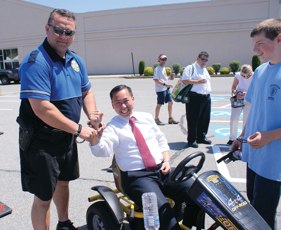 "UNDER ARREST? School Resource Officer Matt Davis from the Cranston Police Department had some fun with Mayor Allan Fung during Cranston Family Safety Day in Garden City after the mayor knocked over more than 15 cones while wearing ""Fatal Vision Goggles,"" which simulates driving under the influence during the daytime."