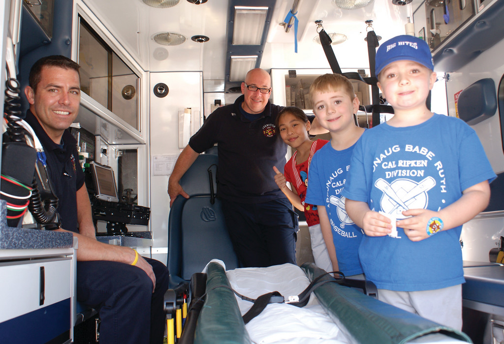 LEARNING ABOUT SAFETY: Discussing rescue operations at the Cranston Fire Department are Pvt. Kevin O'Leary and Cpt. Paul Casey speaking with 10-year-old Peacey Peov and 6-year-old twins Baxter and Benjamin Tietze.
