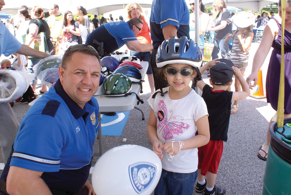 PERFECT FIT: The first 500 children to arrive at Cranston Family Safety Day received free bicycle helmets. Pictured is School Resource Officer Matt Davis fitting 6-year-old Aaliyah Delgado with a new bicycle helmet.