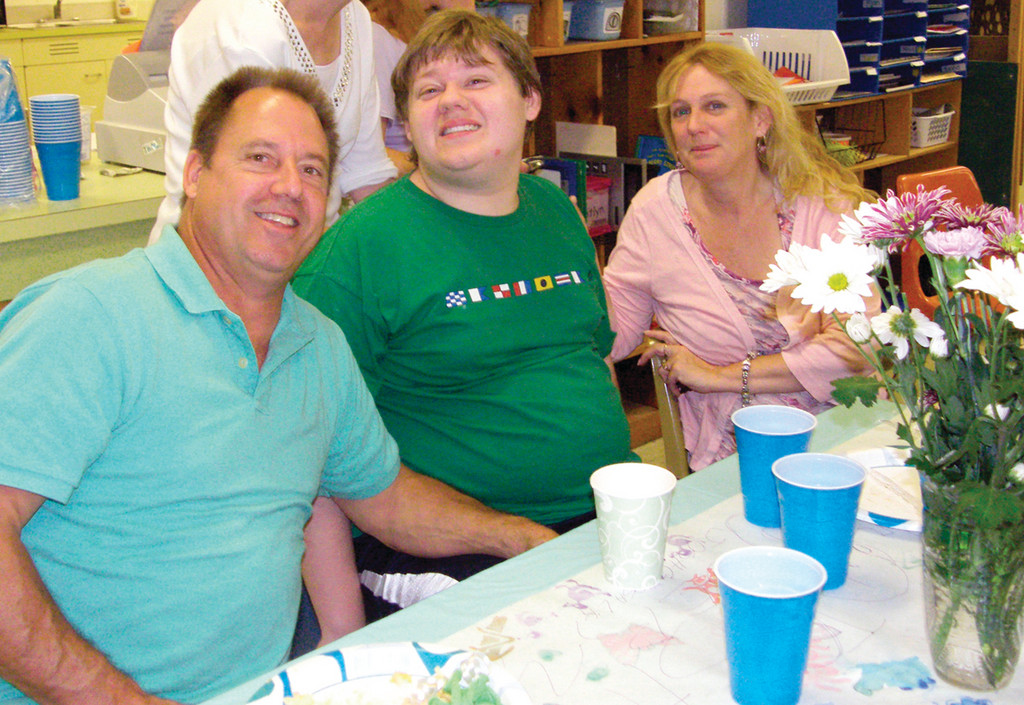 SUNNY SMILES: Josh Germain (center), a Toll Gate student, helped prepare the May Breakfast in his Growth Opportunities class. He is flanked by his proud parents, Ed and Joan, who attended the breakfast.