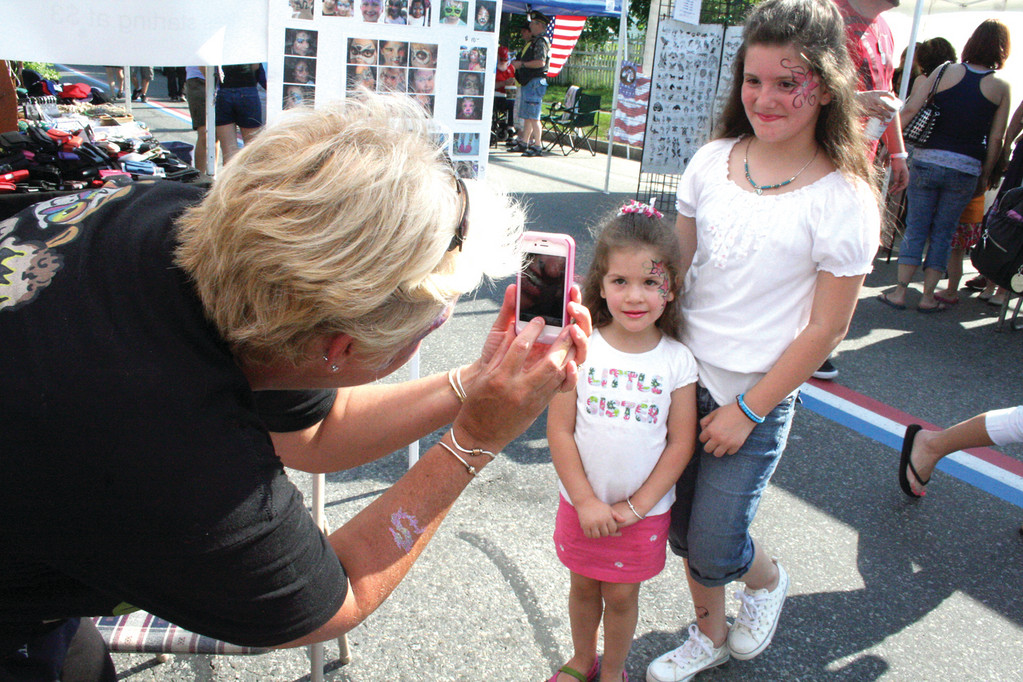 IN FULL BLOOM: Artist Toni Andersen of Wow Face Art snaps a shot of her handiwork on the faces of Hannah Fidas and her younger sister Alexis to post on Facebook. The Andersens and Fidas are neighbors and regulars at the festival.