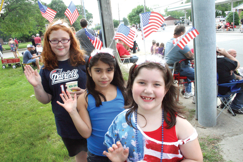Nodding their approval (and waving their flags) are, from left, Haley Gonnella, Natalia Camara and Allison Rodrigues, all third grade classmates at Hoxsie School.