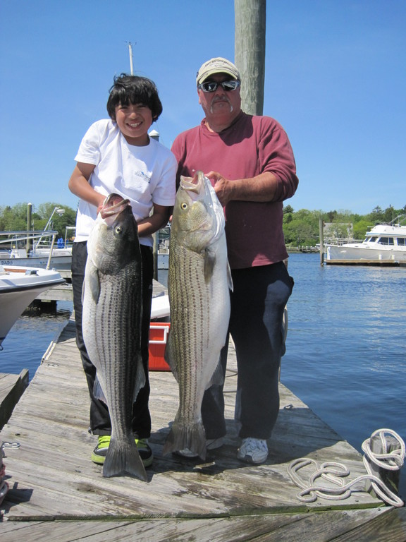Shane Bettencourt (left) of East Providence with the 27 pound striped bass he caught off Prudence Island using live menhaden. His grandfather, Albert Bettencourt (right), landed a 25-pound striped bass that same day.