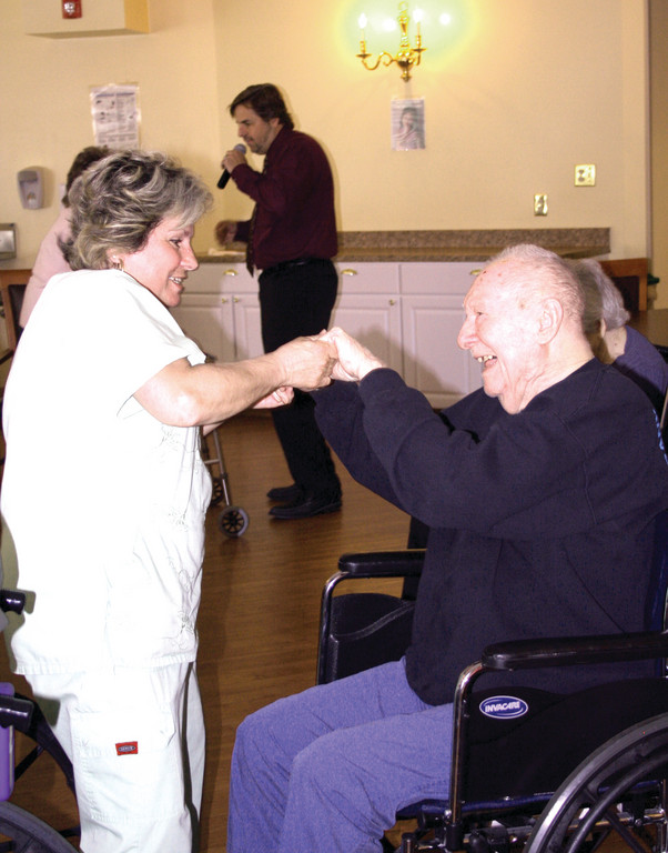 SPREADING CHEER: Activities Aid Gerri Rave gets resident Eugene Tramonti into the spirit.