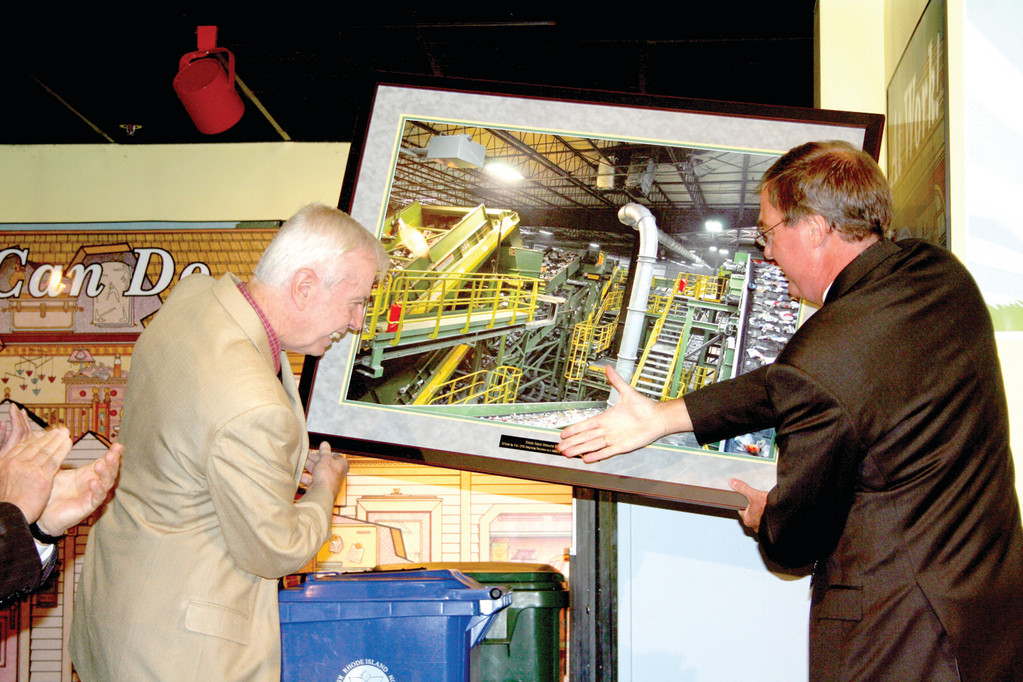 RIRRC Executive Director Michael OConnell accepts a gift from Pieter Van Dyk, founder and president of the Van Dyk Baler Corporation. The enlarged photograph depicts the new sorting system at the Materials Recycling Facility.